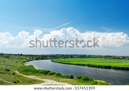 river in green landscape and clouds with blue sky - stock photo