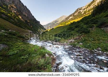 River in mountain valley with bright meadow. Natural summer landscape - stock photo