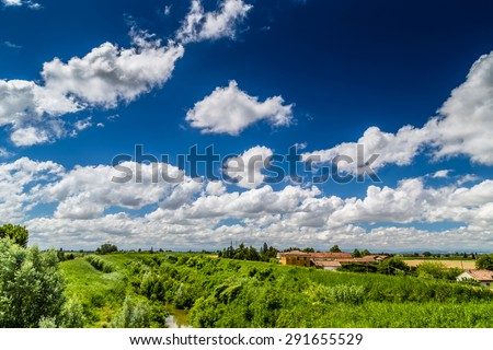 river in the countryside in the north of Italy under a cloudy blue sky