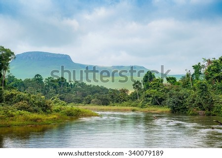 River in the Jungle. Small river in jungle. Under the cloudy sky through hills and mountains the small river proceeds on jungle - stock photo