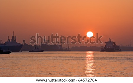 River in the mist with red sunrise, ships and industrial background - stock photo