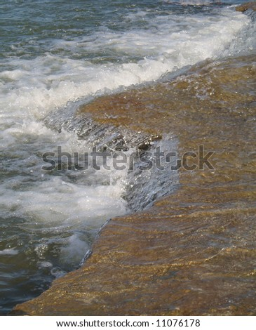 River joining the ocean creating a mini waterfall