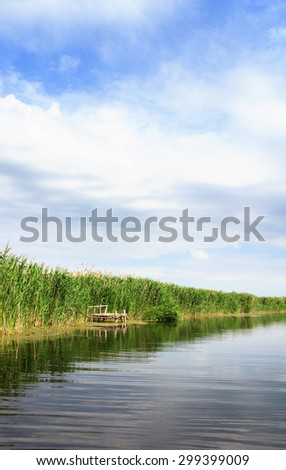 River landscape, clouds in the blue sky, the waves on the water, river, green tourism, travel along the river, boating, summer sunny day after the storm, a harbor for ships, aquatic vegetation. - stock photo