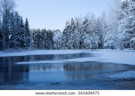 River landscape in winter with tree branches covered with white frost and snow - stock photo