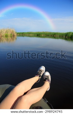 River landscape, rainbow in the blue sky, the girl's legs in sneakers, river, green tourism, travel along the river, boating, summer sunny day, aboard an inflatable boat, aquatic vegetation. - stock photo