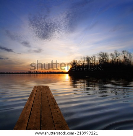 river landscape with wooden pier and sunset on river - stock photo
