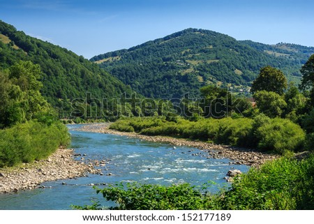 River meanders through the village at the foot of the mountains