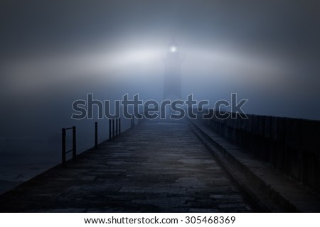 River mouth lighthouse and granite pier in a foggy night - stock photo