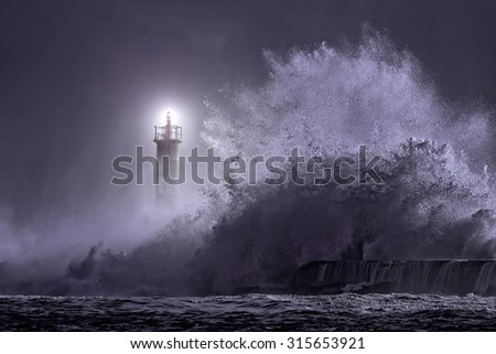 River mouth lighthouse seeing big stormy sea wave at night - stock photo