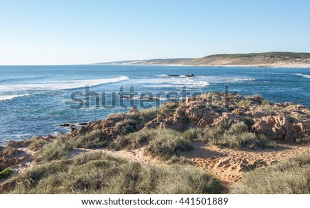 River mouth where the Indian Ocean meets the Murchison river with rocky riverbank and coastal dunes in Kalbarri, Western Australia/River Mouth/Kalbarri, Western Australia - stock photo