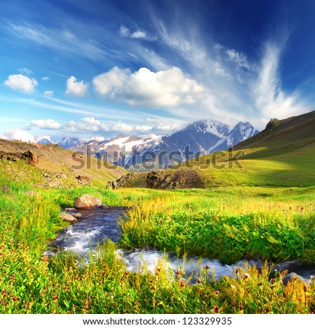 River on bright green meadow. High mountain and clouds. - stock photo