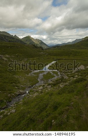 River on dark green meadow. High mountain and clouds.