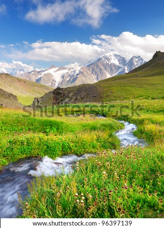 River on green meadow. High mountains and bright sky with clouds - stock photo