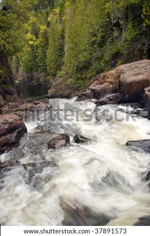 River rapids flow through a gorge on the brule river in northern Minnesota. - stock photo