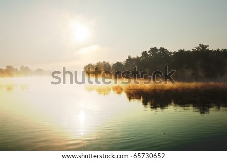 River Rhine in Switzerland is reflecting morning sun rays to the haze - stock photo
