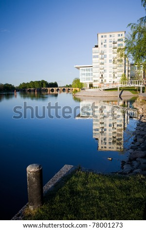 River running through a city in Sweden with modern buldings and a old stone bridge in the background - stock photo