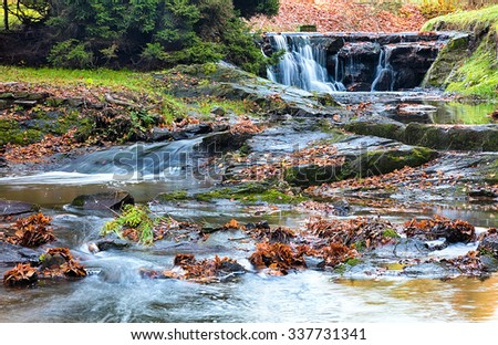 River runs over boulders in the primeval forest - stock photo