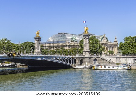 River Seine and the famous bridge Pont Alexandre III. It is an arch bridge that spans Seine, connecting Champs-Elysees quarter and Invalides. Pont Alexandre III is a historical monument. Paris, France