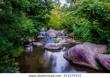 river stream flowing over rock formations in the mountains - stock photo