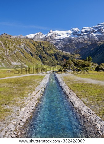 River stream in swiss alp mountains, beautiful green nature landscape, blue sky, sunny day, in the background snowy peaks of famous Titlis mountain, Switzerland - stock photo