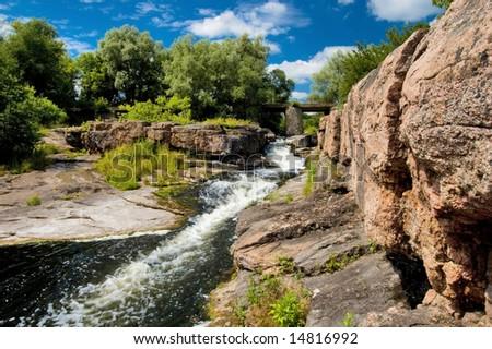River stream with rocks and bridge, sunny day - stock photo