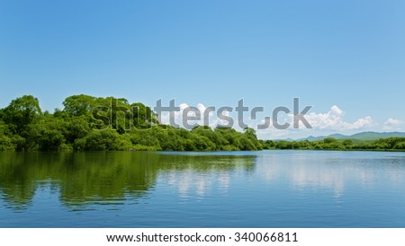 River summer landscape with bright blue sky and clouds. Far East, Russia.