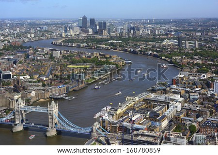 River Thames between Tower Bridge and Canary Wharf with flood barrier distant - stock photo