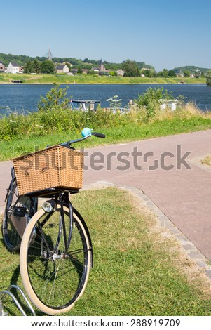 River the Meuse in landscape with Dutch bike in front - stock photo