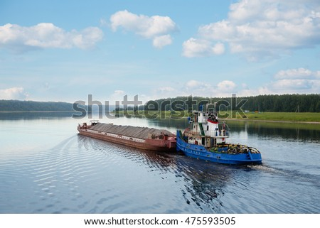 River tugboat moves cargo barge on the Volga river in the summer navigation.