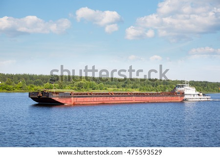 River tugboat moves cargo barge on the Volga river in the summer navigation