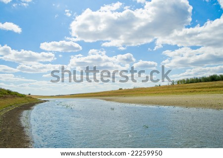 river under cloudy sky - stock photo