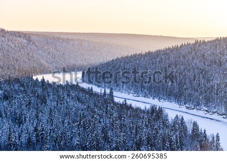 river under the ice, and all around fabulous snowy coniferous forest during sunset - stock photo