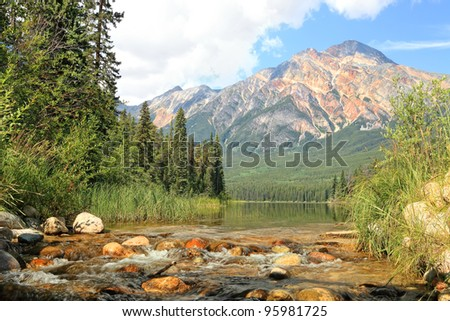 River with a rapid current in a valley between mountains in Jasper National Park (Alberta, Canada) - stock photo