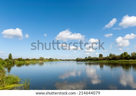 River with blue sky and clouds reflected in water in summer day - stock photo
