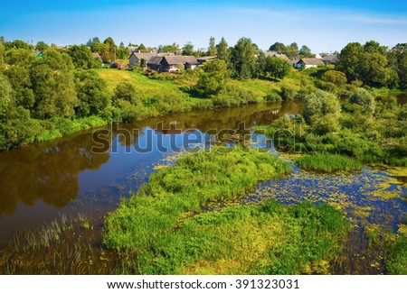 River with thickets of trees and shrubs along the banks. Sunny summer landscape. Calm surface of the water with the reflection of blue sky and vegetation. - stock photo