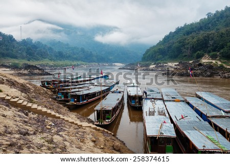 Riverboats along the shore of the Mekong River in Laos - stock photo