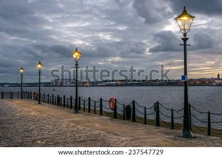 Riverside Cobbled Footpath and Cloudy Sky at Night - stock photo