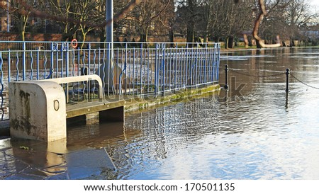 Riverside seats covered in flood water - stock photo