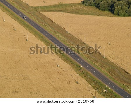 Road across field with telegraph pole with automobile.  Aerial view.