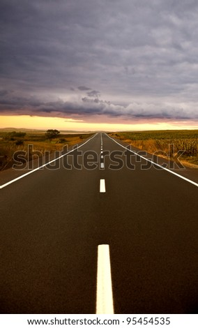 Road ahead close to sunset - stock photo