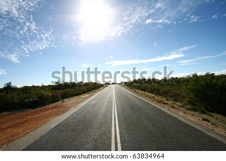 Road ahead with bright spot of sunshine - stock photo
