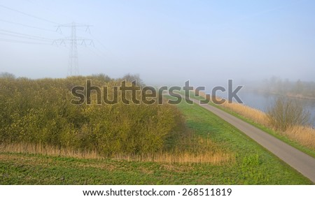 Road along a foggy canal in spring - stock photo