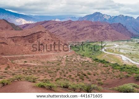 Road along colorful rock formations in Quebrada de Cafayate, Argentina - stock photo