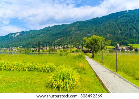 Road along green meadow with alpine village in background in summer landscape of Alps Mountains, Weissensee lake, Austria - stock photo