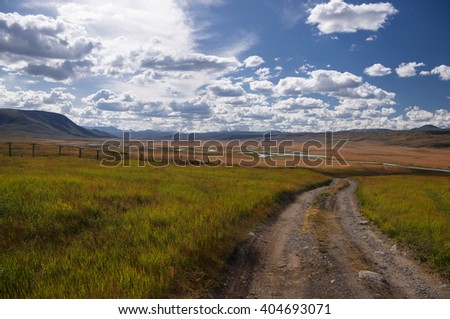 Road along the border line on a highland mountain plateau with the green grass at the background of the valley of white river under a blue sky with white clouds, Plateau Ukok, Altai, Siberia, Russia - stock photo