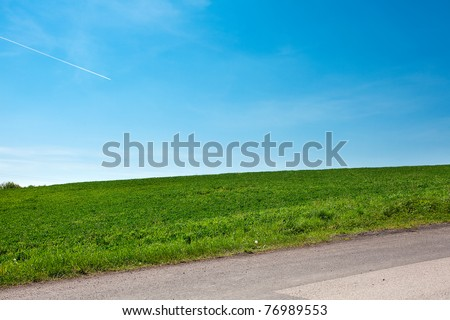 road and a meadow with trees against the blue sky - stock photo