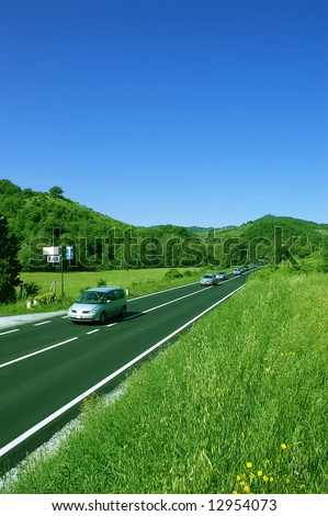 Road and cars between green mountains - stock photo