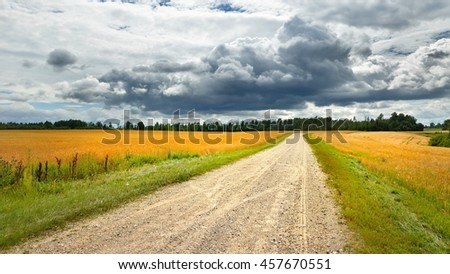 Road and cereal field against dark stormy clouds - stock photo