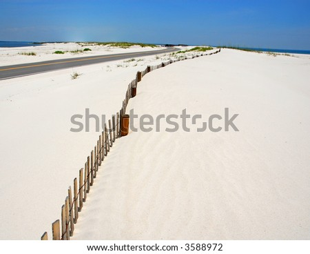 Road and Fence Curving Through Sand Dunes