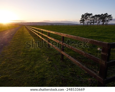 Road and Fence leading straight into the sunset - stock photo